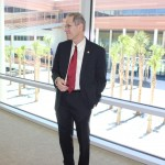 The Dean standing in a corridor overlooking the central plaza.
