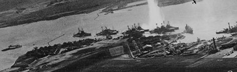 Battleship Row, seen from an attacking Japanese plane. Ford Island is in the foreground.